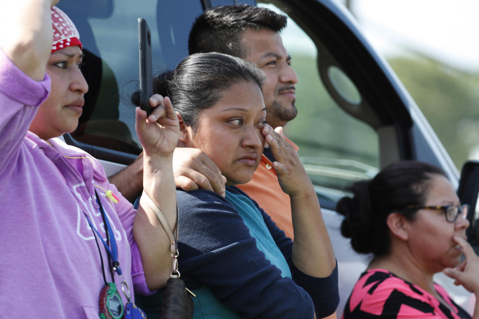 FILE - In this Aug. 7, 2019, file photo, Friends, coworkers and family watch as U.S. immigration officials raid the Koch Foods Inc., poultry processing plant in Morton, Miss. Federal officials announced Thursday, Aug. 6, 2020, the indictments of four executives from two Mississippi poultry processing plants on federal charges tied to one of the largest workplace immigration raids in the U.S. in the past decade. (AP Photo/Rogelio V. Solis, File)