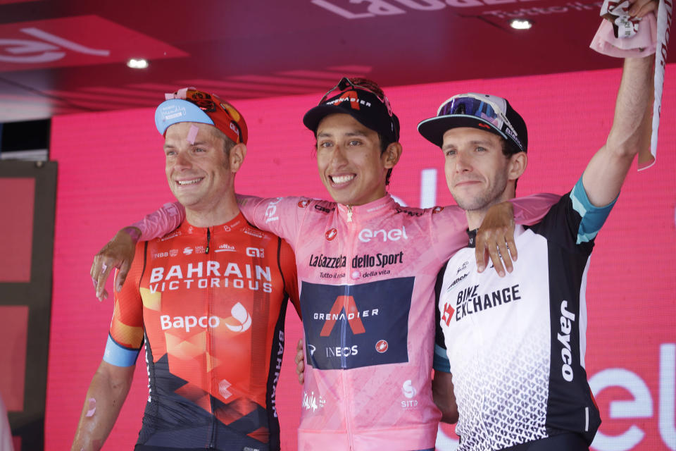 Colombia's Egan Bernal is flanked by runner-up Italy's Damiano Caruso, and Third placed Britain's Simon Yates, right, as he celebrates on podium after completing the final stage to win the Giro d'Italia cycling race, in Milan, Italy, Sunday, May 30, 2021. (AP Photo/Luca Bruno)