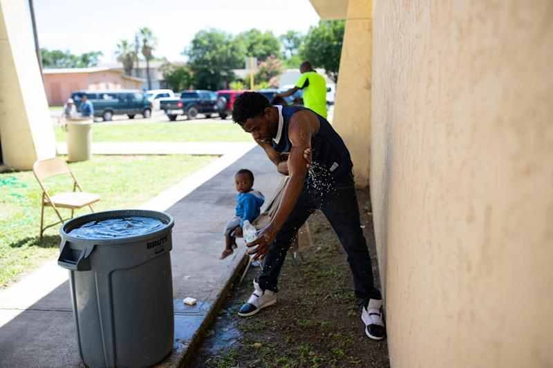 DEL RIO, Texas – A migrant washes himself using runoff water collected from a broken air-conditioning unit at the Val Verde Border Humanitarian Coalition Center on June 25, 2019. He waited at Val Verde for a bus to the San Antonio Migrant Resource Center.