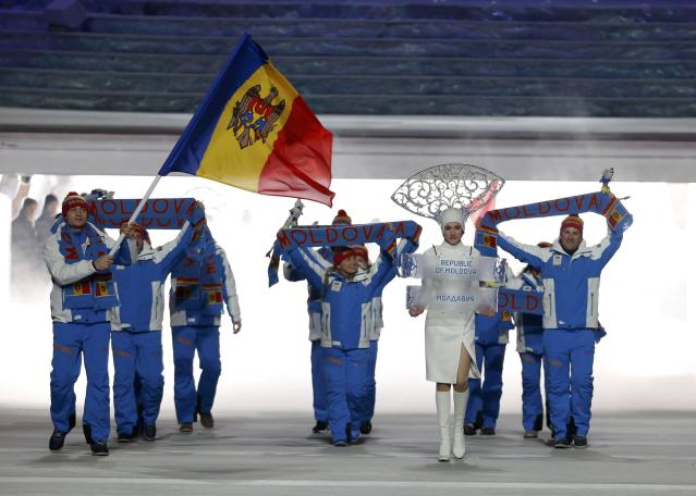 Moldova's flag-bearer Victor Pinzaru leads his country's contingent during the athletes' parade at the opening ceremony of the 2014 Sochi Winter Olympics, February 7, 2014. REUTERS/Phil Noble (RUSSIA - Tags: OLYMPICS SPORT)
