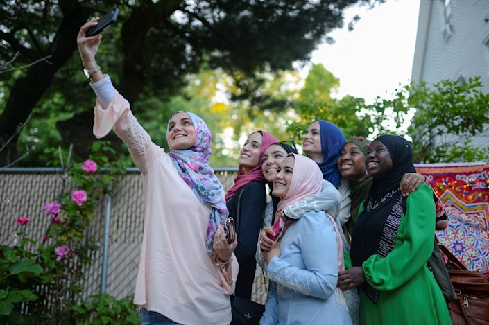 Dina Sayedahmed, an Egyptian American Muslim with a major in journalism and political science from Rutgers University, is embraced as she poses for a selfie in her family's backyard in preparation for her graduation celebration and Iftar feast during Ramadan in Bayonne, New Jersey, U.S. June 2, 2017. Picture taken June 2, 2017. REUTERS/Amr Alfiky