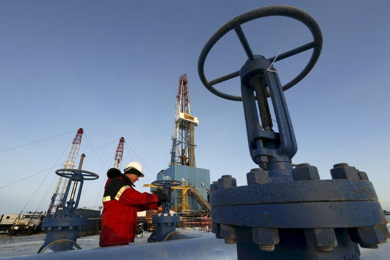 A worker checks an oil pipe at the Lukoil-owned Imilorskoye oil field outside the West Siberian city of Kogalym