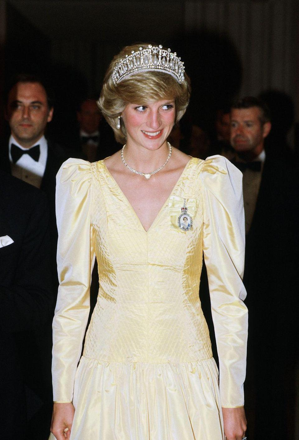 <p>In a yellow satin dress, the pearl-and-diamond Cambridge Tiara, and a heart-shaped necklace given to her by Prince Charles after the birth of their first son, while attending a banquet in Canada.</p>