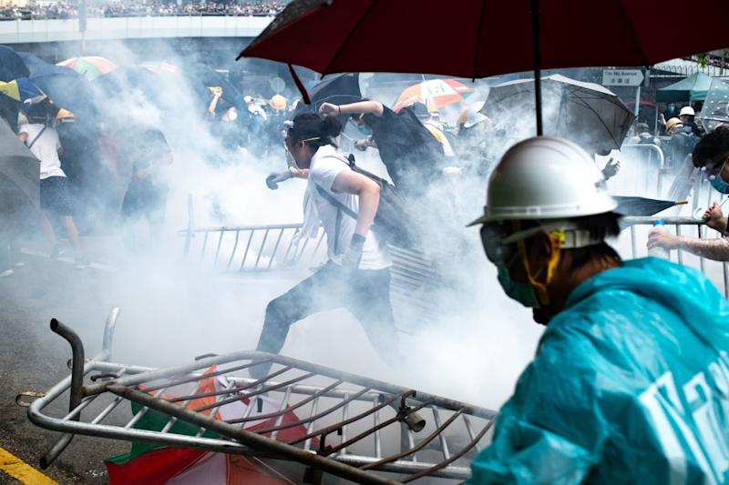 Protesters run after police fired tear gas during a rally against a controversial extradition law proposal outside the government headquarters in Hong Kong on June 12, 2019. | Philip Fong—AFP/Getty Images