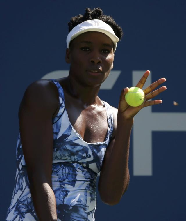 Venus Williams of the U.S. reacts an insect while preparing to serve to Kimiko Date-Krumm of Japan during their match at the 2014 U.S. Open tennis tournament in New York, August 25, 2014. REUTERS/Mike Segar (UNITED STATES - Tags: SPORT TENNIS)