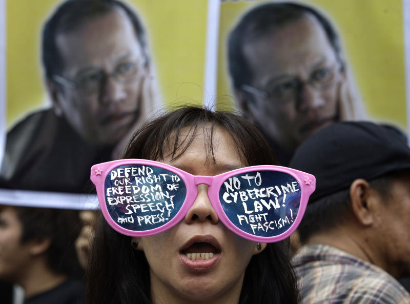 A protester, wearing sunglasses with slogans, stands in front of picture of Philippine President Benigno Aquino III during a rally against the anti-cybercrime law in front of the Supreme Court in Manila, Philippines on Tuesday, Oct. 9, 2012. The Philippine Supreme Court on Tuesday suspended implementation of the country's anti-cybercrime law while it decides whether certain provisions violate civil liberties. (AP Photo/Aaron Favila)