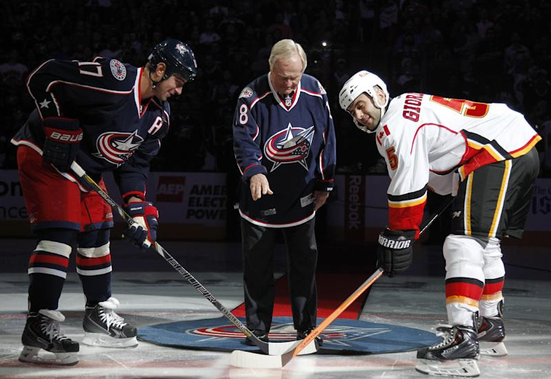 Jack Nicklaus, center, drops the puck between Columbus Blue Jackets' Brandon Dubinsky, left, and Calgary Flames' Mark Giordano during the opening ceremony before an NHL hockey game in Columbus, Ohio, Friday, Oct. 4, 2013. (AP Photo/Paul Vernon)