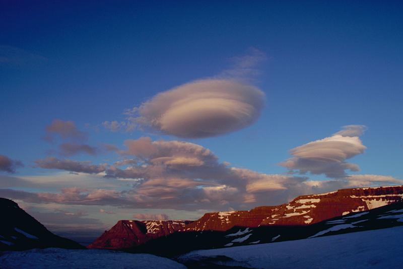 Puffs of cloud float over a mountain range and glaciers, near Skalavik, Iceland.