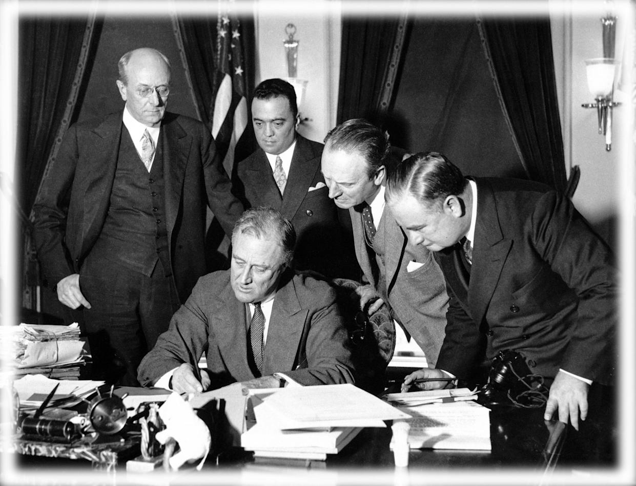 FBI Director J. Edgar Hoover, standing second from left, looks on as President Franklin Delano Roosevelt signs a 1934 bill to enforce the fight against crime. (Photo: Bettmann Archive/Getty Images, digitally enhanced by Yahoo News)
