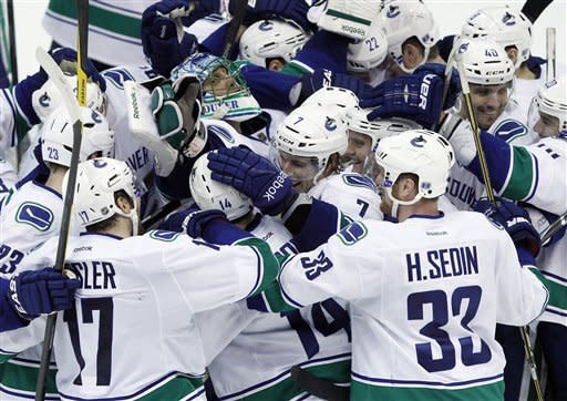 Vancouver Canucks right wing Alex Burrows (14) and goalie Roberto Luongo are mobbed by teammates after Burrows scored the winning goal in a shootout against the Detroit Red Wings in an NHL hockey game in Detroit, Thursday, Feb. 23, 2012. Vancouver won 4-3. (AP Photo/Paul Sancya)
