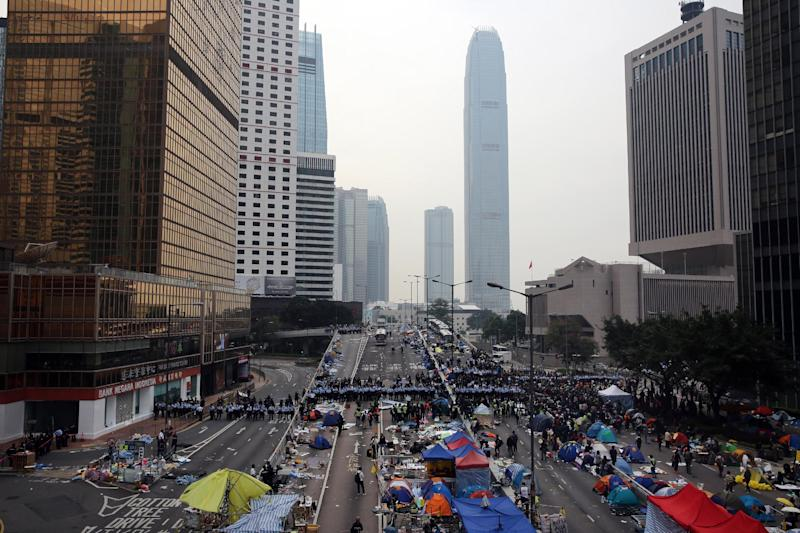 Hong Kong police (centre, in blue) begin to clear the main pro-democracy protest site in Admiralty on December 11, 2014 (AFP Photo/Isaac Lawrence)