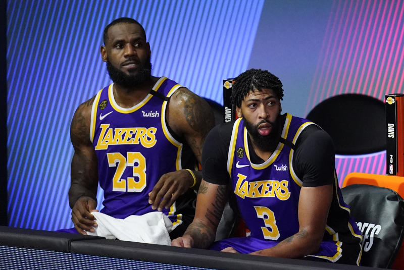 LeBron James, left, in a purple No. 23 Lakers jersey and Anthony Davis, next to him on the bench, in the No. 3.