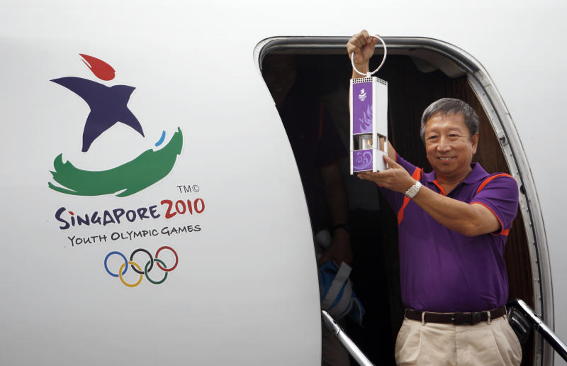 FILE - In this Thursday, Aug. 5, 2010 file photo, Singapore Youth Olympic Committee Chairman and IOC Vice-President, Ng Ser Miang arrives at the Singapore Changi Airport with a safety lantern containing the Youth Olympic flame.  Singapore's Ng Ser Miang is set to become the second declared candidate in the race to succeed Jacques Rogge as president of the IOC. everal officials with knowledge of the decision told The Associated Press on Tuesday, May 14, 2013,  that the 64-year-old Ng will formally announce his candidacy in Paris on Thursday. The officials spoke on condition of anonymity because the announcement hasn't been made yet. (AP Photo/Wong Maye-E, File)