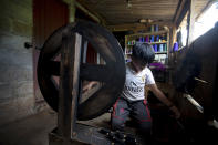 Juan Gabriel Vazquez spins thread at his home while schools are closed amid the new coronavirus pandemic in the community of Nuevo Yibeljoj, Chiapas state, Mexico, Friday, Sept. 11, 2020. Since schools closed in March, the 11-year-old is one of 12 siblings who work in the coffee fields daily instead of just the weekends, while his father helps them with school work dropped off by teachers. (AP Photo/Eduardo Verdugo)