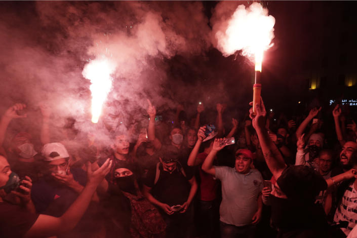 Anti-government protesters light flares as shout slogans against the Lebanese government during a protest in Beirut, Lebanon, Saturday, Oct. 19, 2019. The blaze of protests was unleashed a day earlier when the government announced a slate of new proposed taxes, including a $6 monthly fee for using Whatsapp voice calls. The measures set a spark to long-smoldering anger against top leaders from the president and prime minister to the numerous factional figures many blame for decades of corruption and mismanagement. (AP Photo/Hassan Ammar)