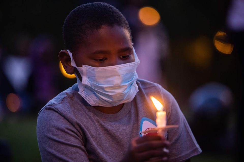 A boy holds a candle during a vigil on June 13, 2020 for Robert Fuller, a 24-year-old black man found hanged from a tree in Palmdale, California.