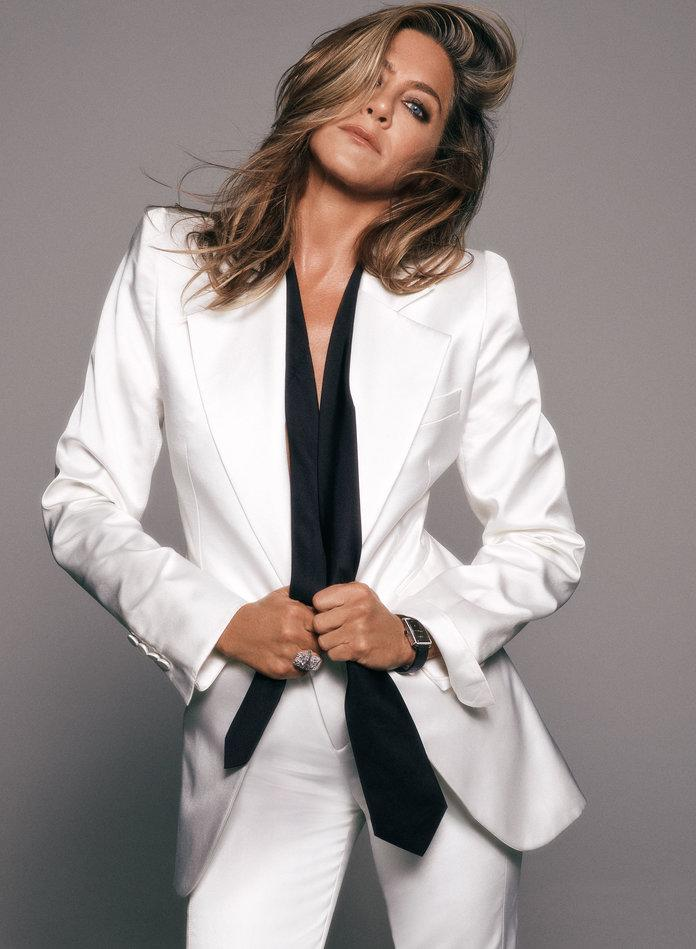 <p>Aniston in a Saint Laurent by Anthony Vaccarello jacket and trousers, a Giorgio Armani tie, a&nbsp;Chanel watch, and a&nbsp;Chanel Fine Jewelry ring. Photographed by Michael Thompson.</p>