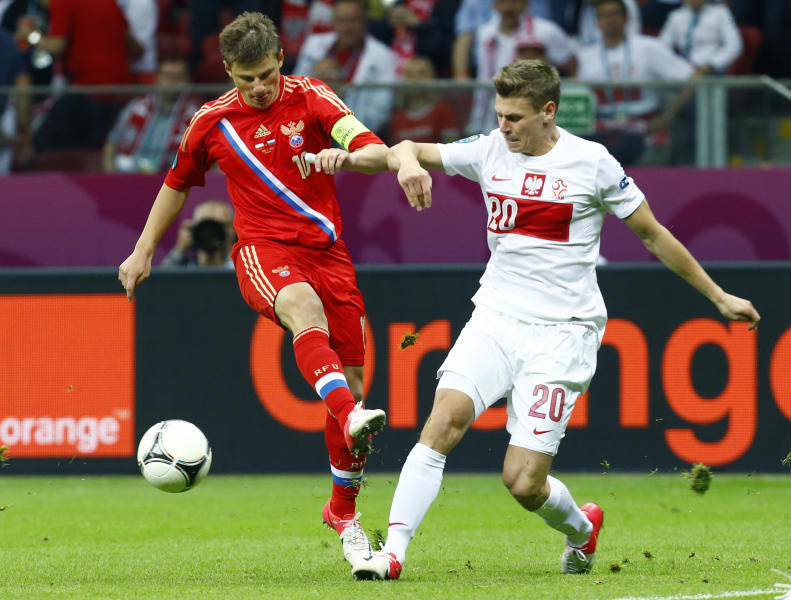Russia's Andrei Arshavin, left, and Poland's Lukasz Piszczek vie for the ball during the Euro 2012 soccer championship Group A match between Poland and Russia in Warsaw, Poland, Tuesday, June 12, 2012. (AP Photo/Sergey Ponomarev)