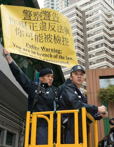 A policeman holds a sign as they watch a protest by pro-democracy activists during the Hong Kong chief executive election