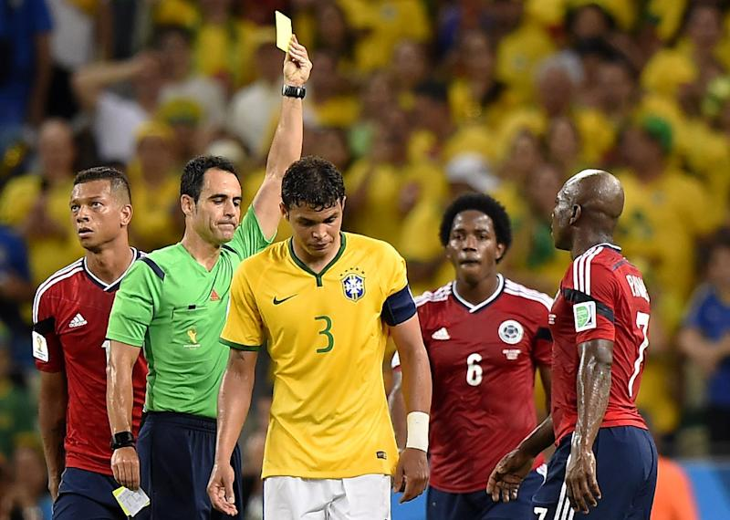 Brazil's captain Thiago Silva (centre) receives a yellow card during the World Cup quarter-final against Colombia at the Castelao Stadium in Fortaleza, on July 4, 2014