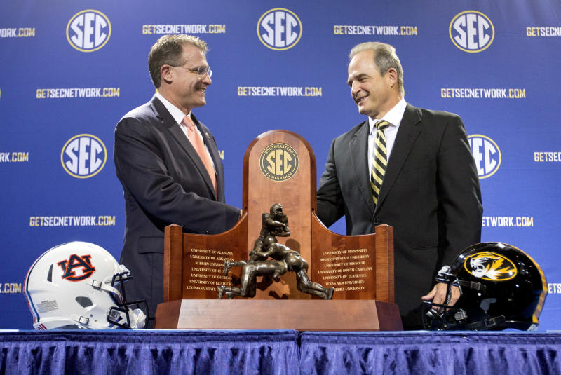 Auburn head coach Gus Malzahn, left, shakes hands with Missouri head coach Gary Pinkel during a photo op at a press conference ahead of Saturday's Southeastern Conference championship football game, Friday, Dec. 6, 2013, in Atlanta. (AP Photo/David Goldman)