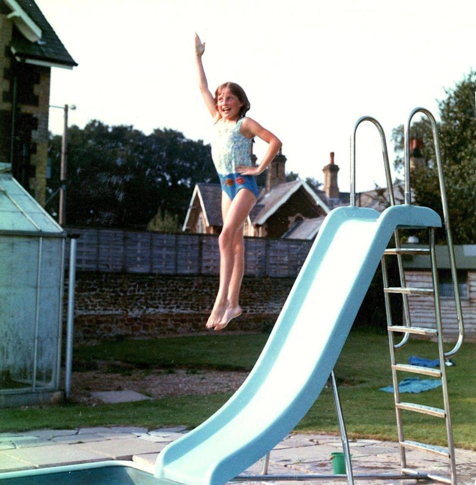 <p>Always poised, even when jumping off a slide into the family's pool at Park House, a youthful Diana shows off her fun side. Her red swimming badges can be seen at the bottom of her bathing suit.</p>