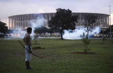 A native Brazilian stands in front of the Mane Garrincha soccer stadium as police use tear gas to impede a group of Indians from approaching it during a demonstration in Brasilia, May 27, 2014. REUTERS/Lunae Parracho
