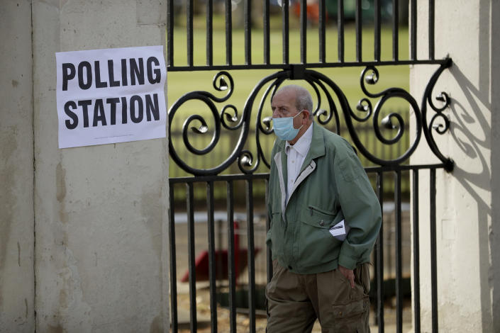 A men wearing a surgical mask to curb the spread of coronavirus walks past a sign for a polling station as he arrives to vote in London, Thursday, May 6, 2021. Millions of people across Britain will cast a ballot on Thursday, in local elections, the biggest set of votes since the 2019 general election. A Westminster special-election is also taking place in Hartlepool, England. (AP Photo/Matt Dunham)