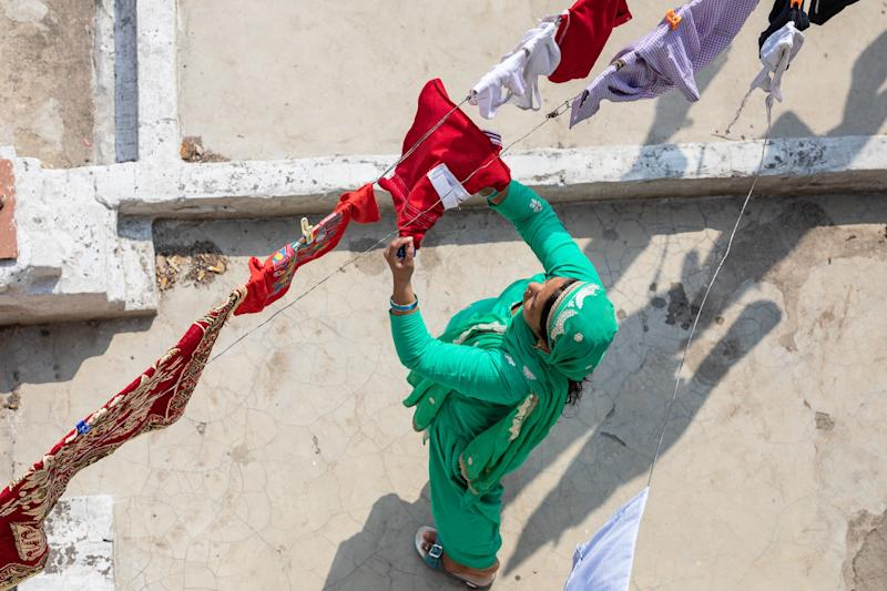 A woman hangs out laundry to dry in the sun on her roof in the City of Agra, India, close to the Taj Mahal.