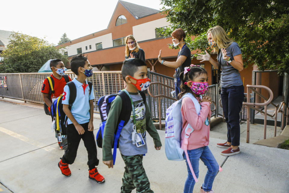 From left to right back, teachers Amy Husk, Noemí Sánchez-Ortíz and Michelle Lovejoy welcome students back on the first day of school, Tuesday, Aug. 25, 2020, at Avon Elementary School in Avon, Colo., amid the coronavirus pandemic. (Chris Dillmann/Vail Daily via AP)