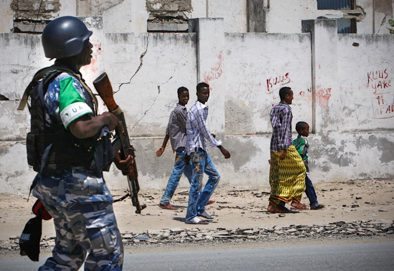Somali youths look on as they walk past a Ugandan police officer serving as part of a Formed Police Unit (FPU) with the African Union Mission in Somalia (AMISOM) walks past during a foot patrol in Mogadishu on November 9, 2012