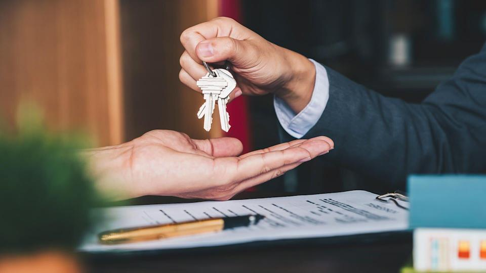 the real estate agent gives the keys to the house to the woman and signs the contract in the office.