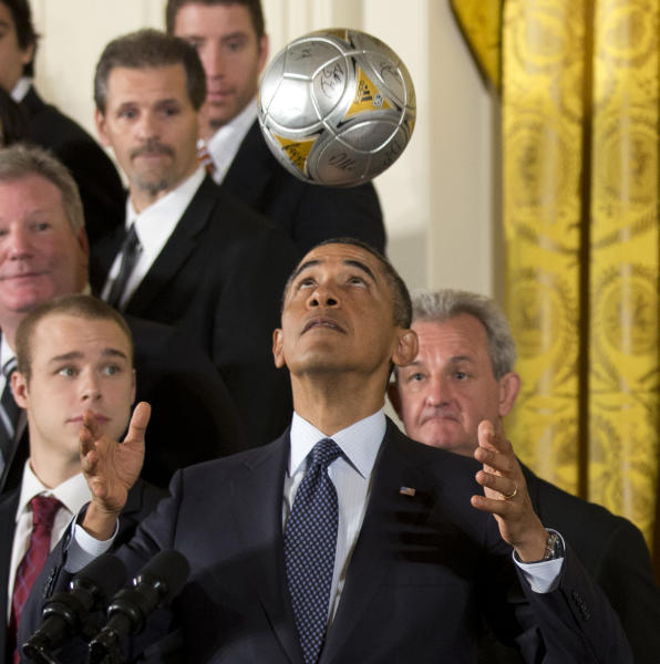 Los Angeles Kings hockey coach Darryl Sutter, right, and others, watch as President Barack Obama bounces the soccer ball off his forehead during a ceremony in the East Room of the White House in Washington, Tuesday, March 26, 2013, honoring the Stanley Cup champion Los Angeles Kings and the Major League Soccer champion LA Galaxy for their 2012 championship seasons. (AP Photo/Manuel Balce Ceneta)