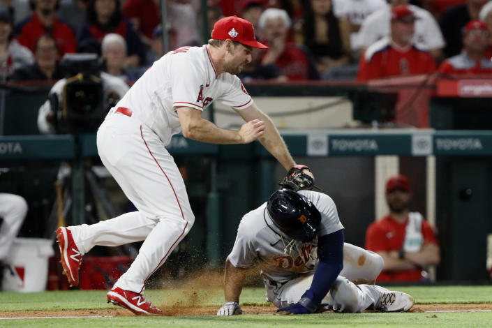 Los Angeles Angels third baseman Phil Gosselin, left, tags out Detroit Tigers' Niko Goodrum in a rundown between third base and home during the seventh inning of a baseball game in Anaheim, Calif., Thursday, June 17, 2021. (AP Photo/Alex Gallardo)