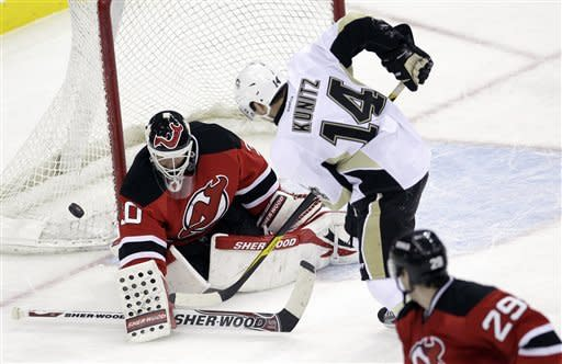 New Jersey Devils' Martin Brodeur (30) makes a save on a shot by Pittsburgh Penguins' Chris Kunitz (14) as Mark Fayne (29) looks on during the third period of an NHL hockey game on Sunday, Feb. 5, 2012, in Newark, N.J. The Devils won 5-2. (AP Photo/Julio Cortez)