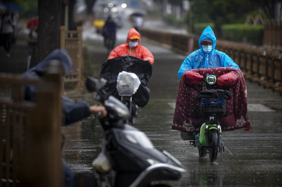 People wearing face masks to protect against the coronavirus ride scooters during a rainfall in Beijing, Wednesday, Aug. 5, 2020. Measures to contain the spread on a COVID-19 outbreak in China's northwestern region of Xinjiang, including locking down some communities and limiting public transport, appear to have been effective and reported case numbers have gradually fallen. (AP Photo/Mark Schiefelbein)