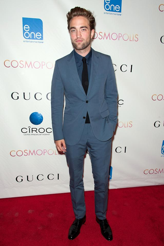 """He may be going through a rough time these days since learning longtime girlfriend Kristen Stewart was cheating on him, but Robert Pattinson is still looking good! In New York on Monday, the """"Twilight"""" hottie walked the red carpet at the premiere of his new flick """"Cosmopolis"""" in a tailored blue Gucci suit he paired with a black tie and his signature scruff. Eat your heart out, KStew! (8/13/2012)"""