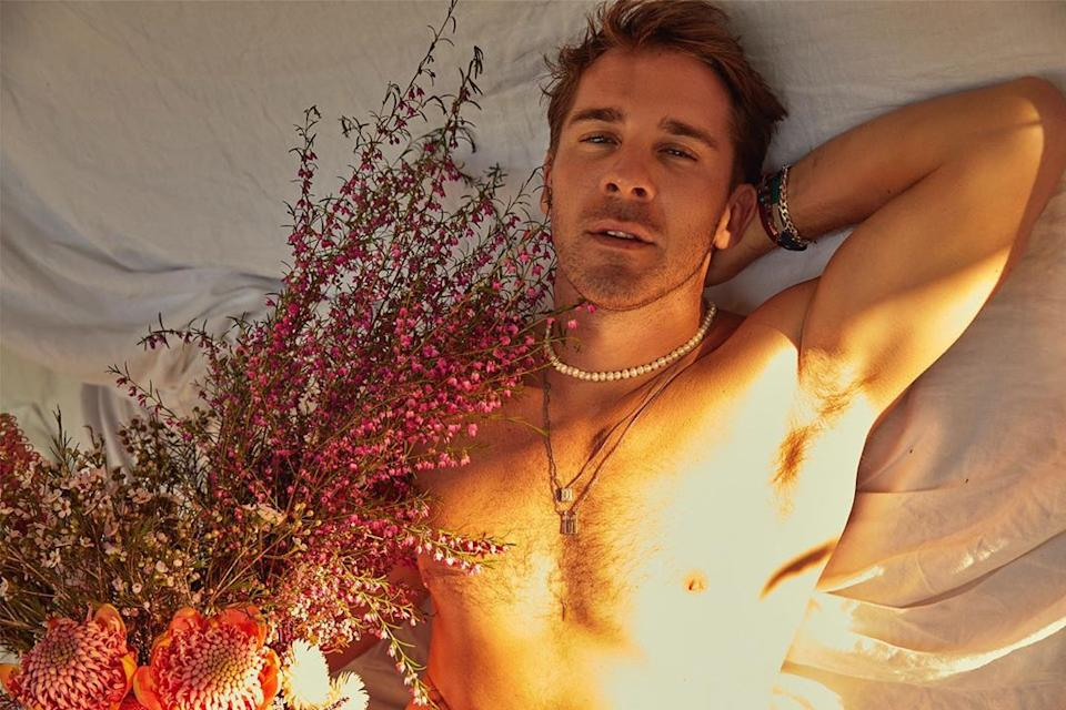 Hugh Sheridan in bed without his top on holding flowers