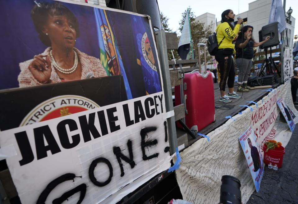 Protesters gather outside the gated Hall of Justice to protest Los Angeles District Attorney Jackie Lacey in downtown Los Angeles, Wednesday, Nov. 4, 2020. Former San Francisco District Attorney George Gascon led two-term incumbent Lacey with 54% of more than 2.7 million votes counted by Wednesday. (AP Photo/Damian Dovarganes)
