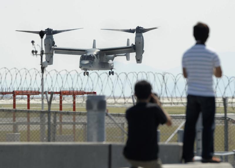Photographers stand as an MV-22 Osprey aircraft takes off from Iwakuni Air Base, Yamaguchi prefecture, southern Japan, Friday, Sept. 21, 2012. The U.S. Marines conducted their first test flights of the MV-22 Osprey aircraft in Japan after months of protests there over safety concerns. (AP Photo/Kyodo News) JAPAN OUT, MANDATORY CREDIT, NO LICENSING IN CHINA, HONG KONG, JAPAN, SOUTH KOREA AND FRANCE