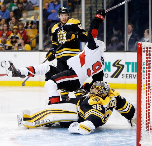 Ottawa Senators' Bobby Ryan (9) collides with Boston Bruins' Anton Khudobin (35), of Kazakhstan, during the third period of an NHL hockey game in Boston, Saturday, April 7, 2018. The Bruins won 5-2. (AP Photo/Michael Dwyer)