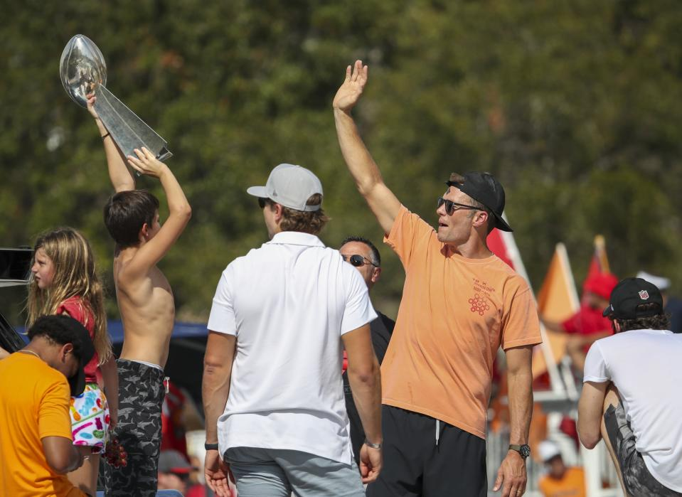 Tampa Bay Buccaneers NFL football quarterback Tom Brady, right, waves as an unidentified boy holds the Lombardi Trophy as he and others celebrate their Super Bowl 55 victory over the Kansas City Chiefs with a boat parade in Tampa, Fla., Wednesday, Feb. 10, 2021. (Dirk Shadd/Tampa Bay Times via AP)