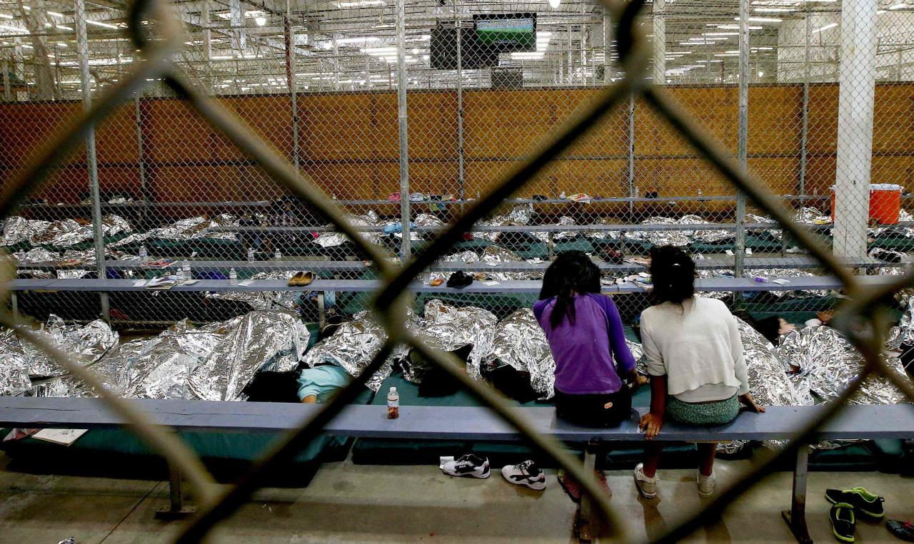 Two young girls watch a World Cup soccer match on a television from their holding area where hundreds of mostly Central American immigrant children are being processed and held at the U.S. Customs and Border Protection Nogales Placement Center in Nogales, Arizona June 18, 2014. CBP provided media tours June 18 of two locations in Brownsville, Texas and Nogales that have been central to processing the more than 47,000 unaccompanied children who have entered the country illegally since Oct. 1. REUTERS/Ross D. Franklin/Pool (UNITED STATES - Tags: CRIME LAW POLITICS SOCIETY)