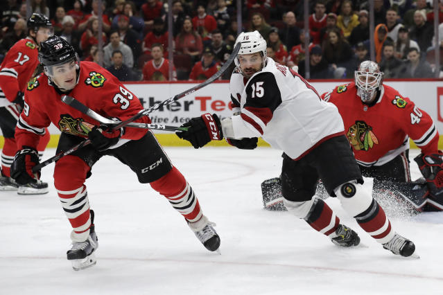 Arizona Coyotes center Brad Richardson, right, and Chicago Blackhawks defenseman Dennis Gilbert chase as they battle for the puck during the first period of an NHL hockey game Sunday, Dec. 8, 2019, in Chicago. (AP Photo/Nam Y. Huh)