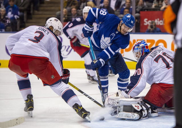 Toronto Maple Leafs left winger Andreas Johnsson (18) moves the puck past Columbus Blue Jackets goaltender Joonas Korpisalo and defenseman Seth Jones (3) during second-period NHL hockey game action in Toronto, Monday, Oct. 21, 2019. (Frank Gunn/The Canadian Press via AP)