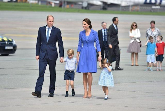 A color-coordinated Kate and William arrive at Berlin Tegel Airport with their children in tow. Kate opted for a waist-fitted royal blue Catherine Walker coat dress that featured two self-covered buttons, three-quarter sleeves, shawl lapels and a pleated skirt. She complemented her look with towering Gianvito Rossi heels and a pulled-back 'do. <em> (Photo: Kensington Palace/Twitter)</em>