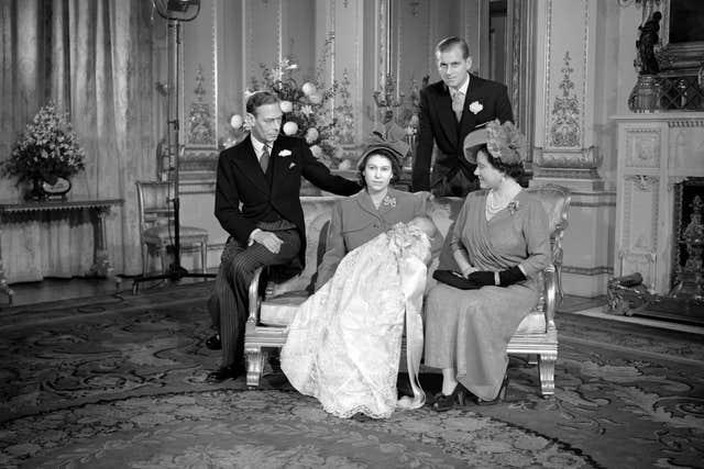 Prince Charles sleeps in the arms of his mother, Princess Elizabeth, after his christening at Buckingham Palace. Looking on are, left, King George VI, the Duke of Edinburgh, and Queen Elizabeth