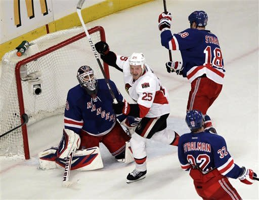 Ottawa Senators' Chris Neil (25) celebrates a goal by teammate Daniel Alfredsson (not shown) during the second period of Game 7 of a first-round NHL hockey Stanley Cup playoff series against the New York Rangers, Thursday, April 26, 2012, in New York. (AP Photo/Julio Cortez)