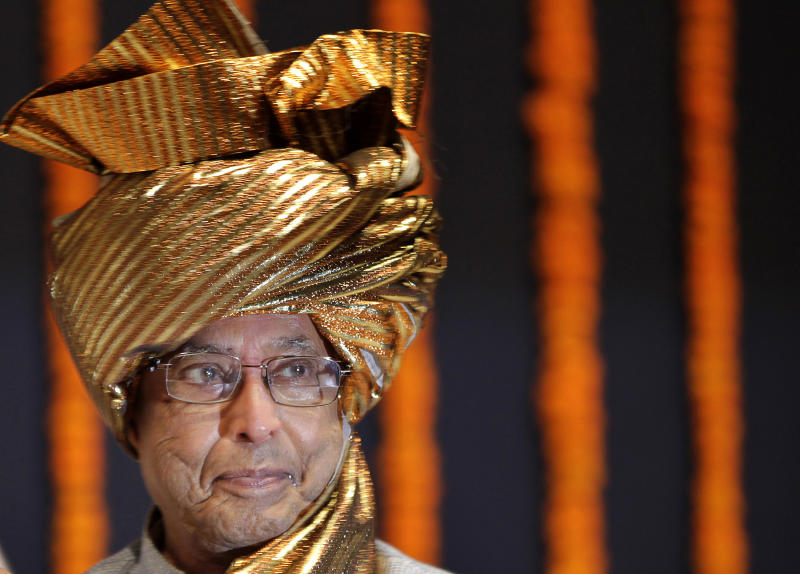 FILE - In this Friday, July 13, 2012 file photo, Pranab Mukherjee, presidential candidate of India's ruling alliance, wears a traditional headgear presented by Congress party members during his visit to meet Maharastra state lawmakers in Mumbai, India. Mukherjee, who spent years whipping coalition partners into shape and quelling scandals as the Congress Party's chief firefighter, seems likely to leave all that behind and become India's figurehead president in an election Thursday, July 18, 2012. (AP Photo/Rajanish Kakade, File)