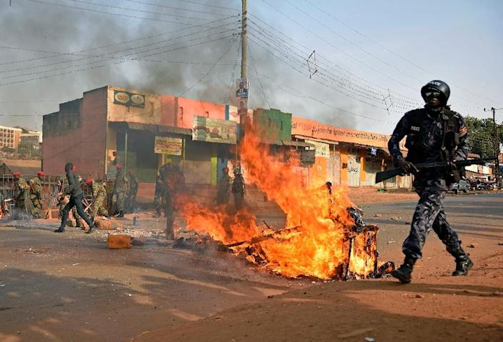Uganda's military police put out a burning barricade lit by opposition supporters in Kampala on February 15, 2016 (AFP Photo/Isaac Kasamani)